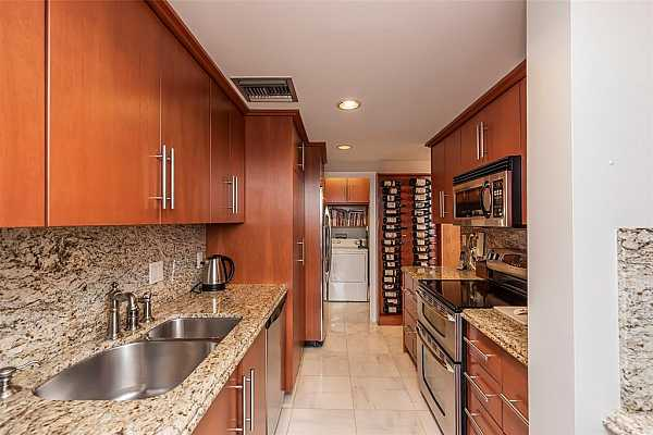 Photo #11 Another view of kitchen with built-in wine rack and utility room for washer, dryer and extra refrigerator.