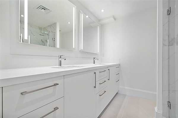 Photo #7 Dual vanities, glass enclosed shower, Eggersman cabinetry and vanity mirror complete this spa like retreat in the primary bedroom.