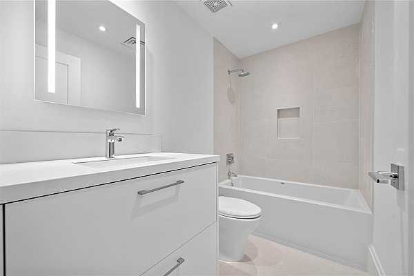 Photo #10 Guest bathroom with deep soaking tub and floating cabinetry.