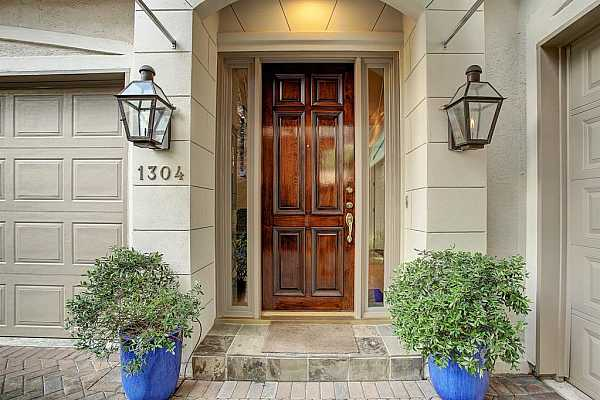 Photo #1 The COVERED FRONT ENTRY is well lit and features slate tile flooring, a solid mahogany front door flanked by glass panels, and elegant carriage lamps.