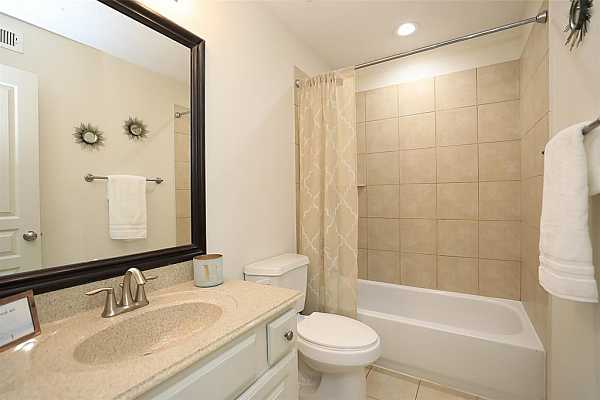 Photo #6 Full Bathroom located on 1st floor. Oversized tiles wrap the walls of the shower/tub combo, lending it an upscale vibe that complements the tones of the vanity.