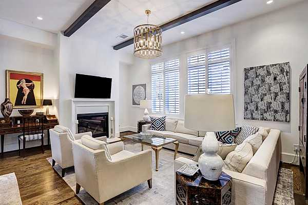 Photo #12 High ceilings, overly abundant natural light, plantation shutters and open stairwell keep the living room vibrant and comfortable for all types of gatherings. Powder room serves second level. (This chandelier is excluded by seller)