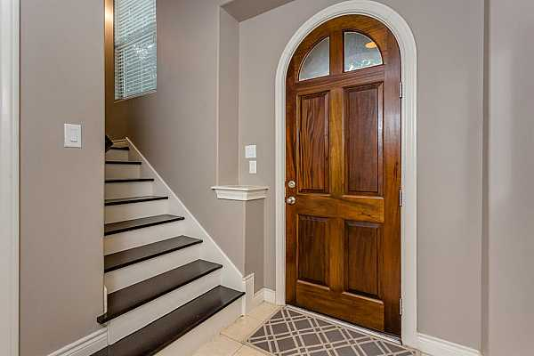 Photo #7 First floor entrance with high ceilings, tile floors and hardwood treads that lead you up to the second floor. On the first floor you will find a bedroom and full bath perfect for in-laws, kids or guests.