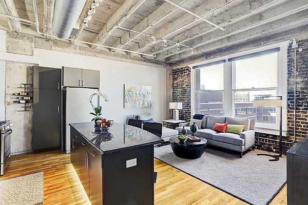 Photo #1 Move right into this meticulously renovated, quintessential loft home filled with extraordinary city views and designer interiors that beg to entertain. Soaring ceilings, hardwood floors and exposed brick, concrete and ductwork underscore the industrial-chic style of this stunning two-bedroom, one-bath Downtown showplace.