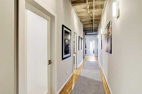 Photo #4 The long gallery entry makes a dramatic first impression with wide art walls, sconces and new frosted glass doors. Here, you