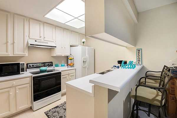Photo #9 Bright & White kitchen complete with stove, hood, microwave, dishwasher, disposal and refrigerator all come with the purchase of the home