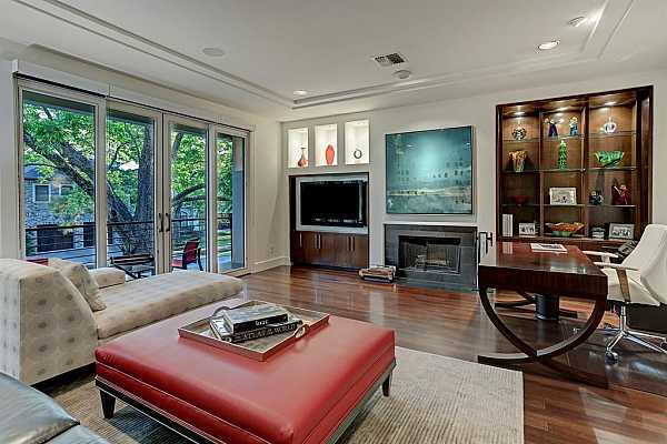Photo #3 Indoor-outdoor living is yours in the expansive living room featuring a wood-burning fireplace and a wall of custom cabinetry with file drawers, cupboards, illuminated glass shelving and art niches.