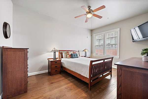 Photo #11 Relax in the haven of this primary suite, with hardwood floors and oversized windows for natural lighting. The room can accommodate a large bed and still have enough space for other furniture.