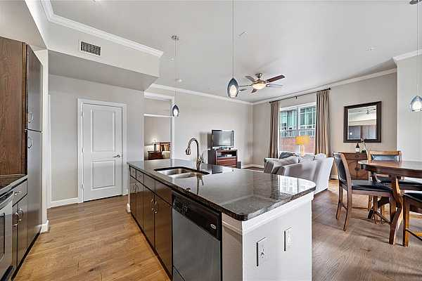 Photo #5 Open concept living at its best! Entertain guests and family as you cook delicious meals in the open kitchen. Notice the sleek floors, soaring ceilings, and crown molding throughout.