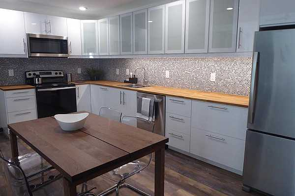 Photo #4 Stainless Appliances, Wood Counters, and Wood and Glass Cabinets with Backsplash and Vinyl Plank Flooring