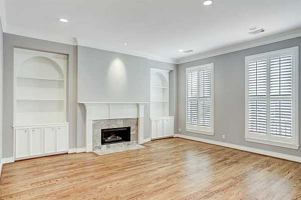 Photo #8 Formal living room with custom plantation shutters, hardwood floors and built in display cases. Wood burning fireplace with gas jet.