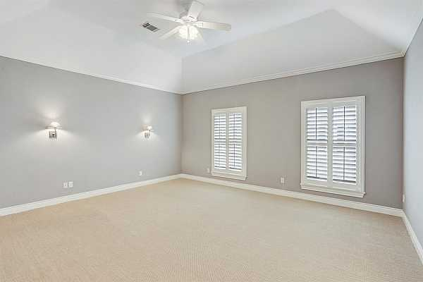 Photo #10 Spacious Primary Bedroom with sisal carpet, custom shutters, wall sconces,  and two generously sized walk-in closets.