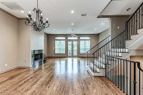 Photo #6 Dramatic light + bright second floor living/dining. Gleaming hardwoods with double doors leading the front balcony. Custom iron chandelier defines the perfect spot for the dining space.