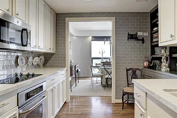 Photo #11 Beautifully remodeled kitchen with wood floors.  Stainless appliances.  Excellent storage space.  Quartz countertops.  Soft close drawers.  Easy care tile walls.