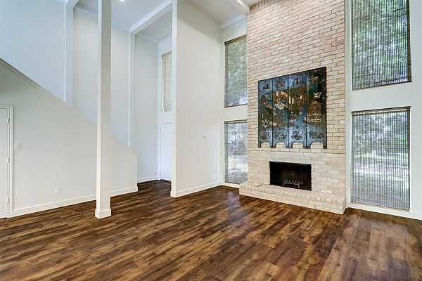 Photo #8 Large windows with custom grass shades, fireplace with brick wall and warm hardwood flooring.