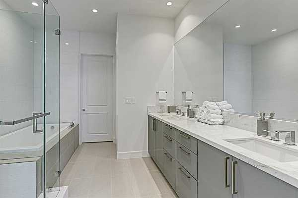 Photo #6 Primary Bathroom - features tile floors, marble countertops, double sinks, large seamless glass shower and separate jetted tub. Door in front leads to walk-in closet with custom shelving.