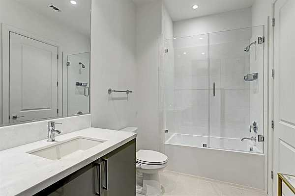 Photo #9 Secondary Bathroom featuring tile floors, marble countertop and seamless glass shower/tub combo.