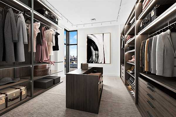 Photo #12 Display your wardrobe in this vast primary closet with a corner window and boutique lighting.