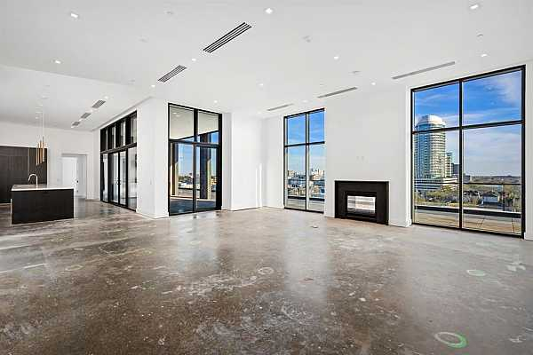 Photo #4 Walk into an exquisitely spacious penthouse living and dining area framed by floor to ceiling windows with panoramic city views.
