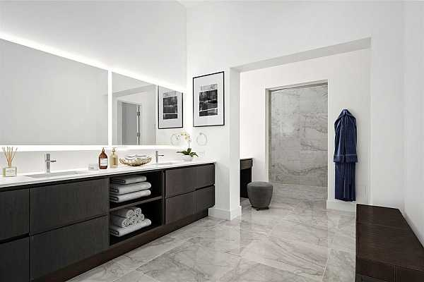 Photo #9 The primary bathroom suite includes a designated vanity, in-mirror lighting, and lush porcelain tile.