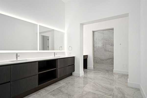 Photo #10 Miles of fine porcelain line the floor of the primary bathroom and the walls of the attached wet room.