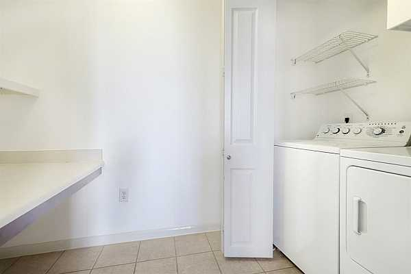 Photo #9 This area also has laundry area with full size appliances and hot water heater behind closed doors.