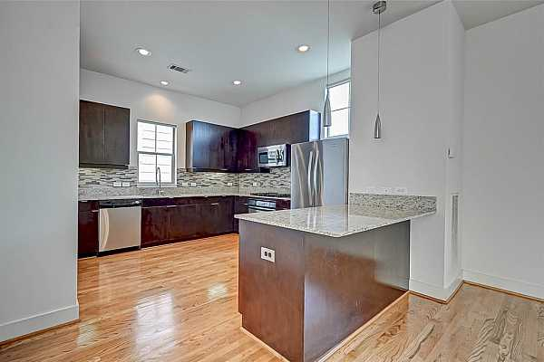 Photo #4 Huge Kitchen with updated glass tile backsplash, new stainless-steel refrigerator with icemaker and bottom freezer is included.