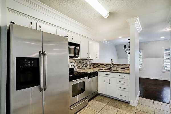 Photo #3 The beautifully updated kitchen has high end appliances, granite counters, a double sink, and a modern backsplash.
