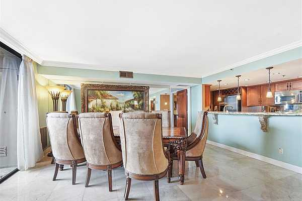 Photo #7 Make memories gathered around the table with your family and friends! This dining room has Marble floors, a wall of mirrors, a wall of full-length windows with privacy blinds, crown molding, and access to the balcony.