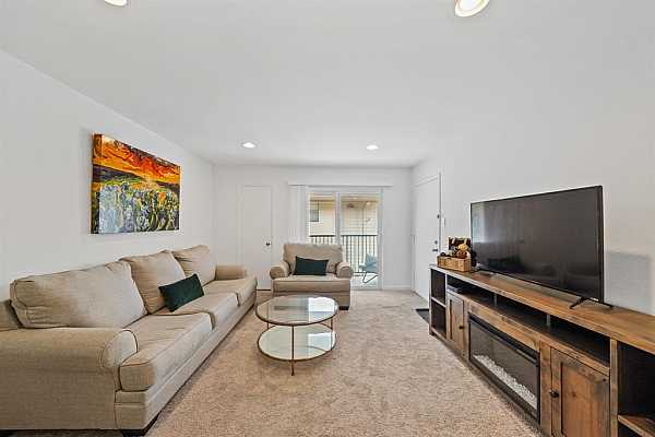 Photo #5 The front door opens to a spacious living room with neutral paint colors, recessed lighting and carpet.