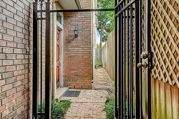Photo #3 The wrought iron entry gate provides additional security, and the side walkway allows easy access to the back patio of this end unit townhome.
