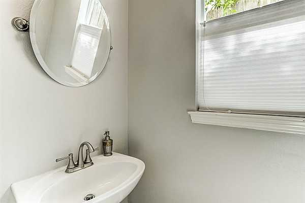 Photo #6 The updated first floor powder room has a pedestal sink with ample natural light and new tile floorin