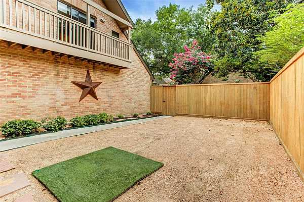 Photo #4 Another view of the generous yard at 214 Sugarberry. The owner recently replaced the fence and added outdoor lighting.