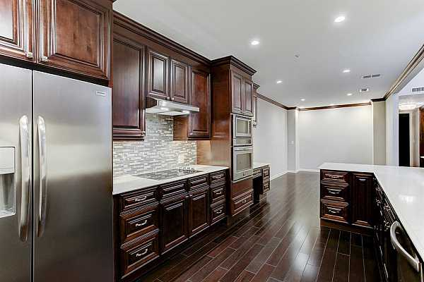 Photo #11 The new appliances include an electric cooktop, microwave, oversized oven and side by side stainless refrigerator which remains.