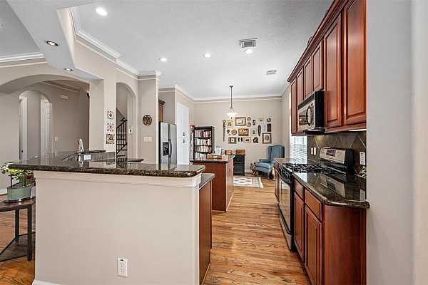 Photo #10 Chef's kitchen boasts granite counters, stainless steel appliances, rich cabinetry & attached breakfast & formal dining area.