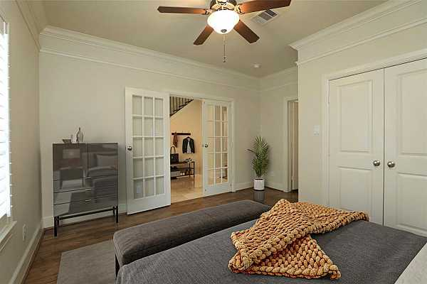 Photo #12 another view of the secondary bedroom with french doors and beautiful hardwood flooring