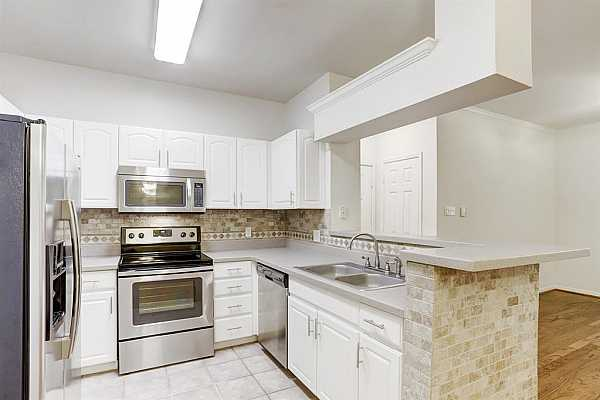 Photo #9 Kitchen with stone backsplash and stainless steel appliances is open to living and dining areas.