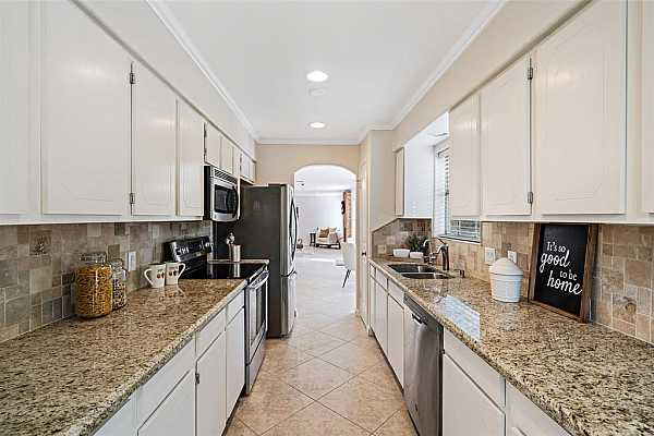 Photo #6 Modern finishes with beautiful white cabinets are hallmarks of this great kitchen. Notice the elegant diagonal tile pattern and an abundance of counter space! Cook your best meals over looking the beautifully landscaped courtyard!