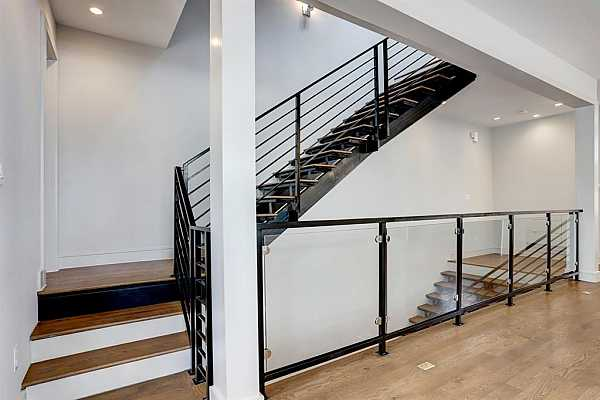 Photo #5 Modern finishes are spread all throughout the home including gorgeous wood flooring and iron hand railing with glass paneling on the staircase.