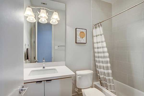 Photo #9 This secondary full bath features a beautiful tile backsplash, a large mirror and storage space.