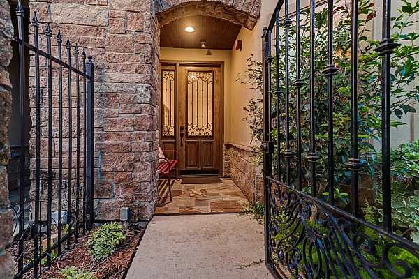 Photo #5 A front electric gate leads into a fully fenced front small patio, featuring stone details, a beautiful custom-built wood front door with glass and wrought iron accents