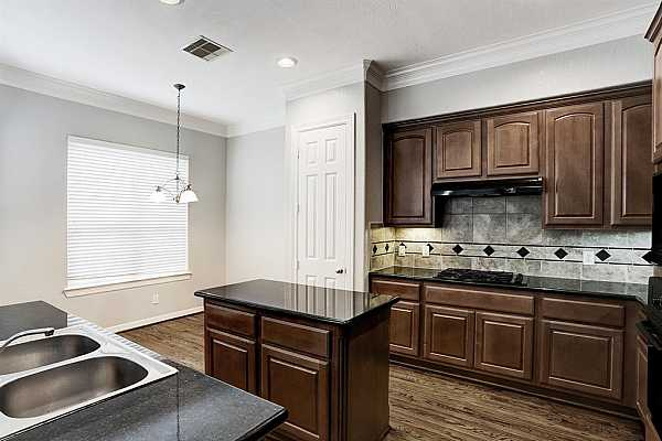 Photo #7 Island kitchen with granite counters, undercabinet lighting with a large open window to the living area.