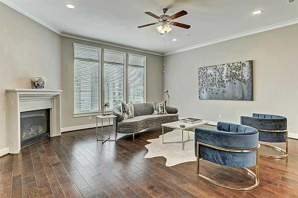 Photo #1 Living Space adds the ambiance of the fireplace , with gleaming hardwood floors, plus natural light and high ceilings.