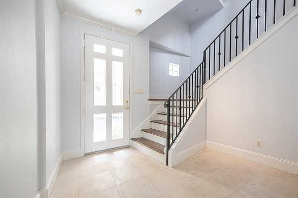Photo #5 As you step inside you are greeted by classic Italian stone floors, elegant wrought iron stair railing and an abundance of natural light pouring in from the mahogany and glass 6 panel door.