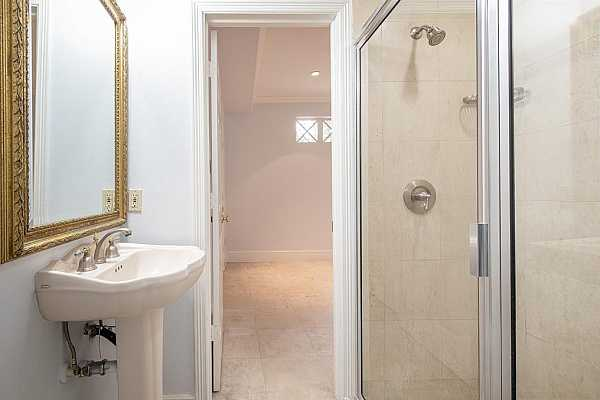 Photo #8 The full bath adjoining the first floor bedroom offers a pedestal sink and shower.