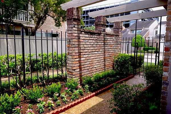 Photo #6 The brick wall and columns are a prized bonus, lending southern style and elegance, all protected by a wrought iron fence and gate for security.