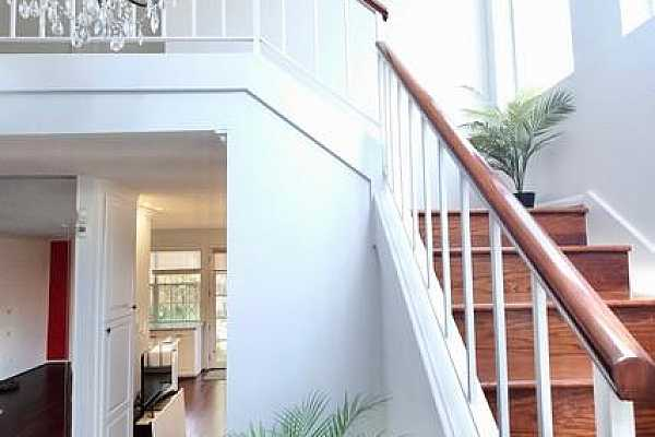 Photo #7 From your elegant entry, hardwood stairs lead to the second floor. This soaring ceiling is brilliant with natural light from north facing picture windows above.