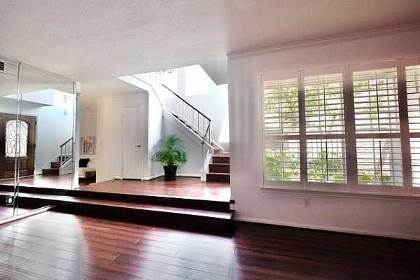 Photo #8 Step down from your dramatic entry to the main living/dining area, dressed for companywith engineered wood floors and a fully mirrored wall at one end.