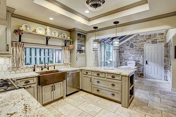 Photo #11 Kitchen features stainless steel appliances, gas range, granite countertops, travertine flooring, and a tray ceiling. The kitchen has great upgraded cabinetry.