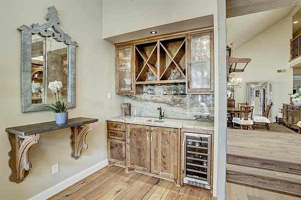 Photo #8 Wet bar with wine cooler, cabinets with glass fronts, wine storage, and granite countertop.